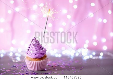 Cupcake with purple cream icing and sparkle on a glitter background