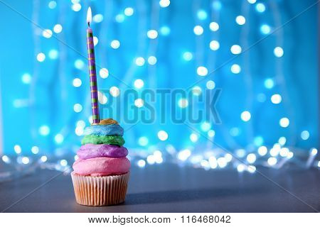 Cupcake with varicolored cream icing and candle on a glitter background