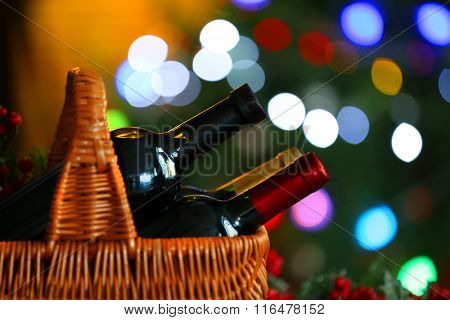 Wine in basket on Christmas tree background, closeup