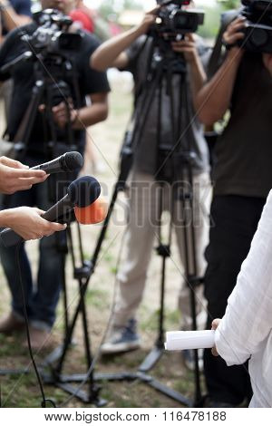 Journalists holding a microphones conducting an TV or radio interview poster