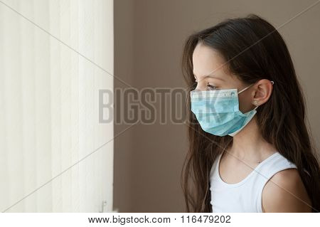 girl standing at the window in the hospital in medical mask