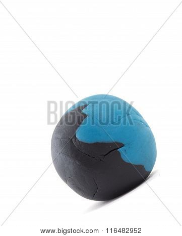 Rolling Blue And Black  Plasticine Ball On White Background