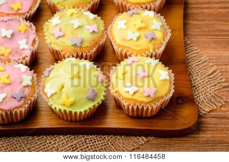 Muffins covered with colorful icing shugar on the wooden board.
