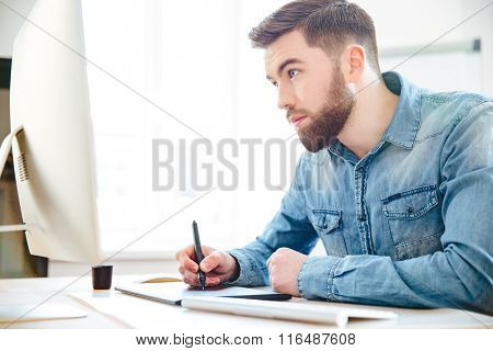 Concentrated handsome young designer with beard in blue shirt drawing using computer and graphic tablet in the office
