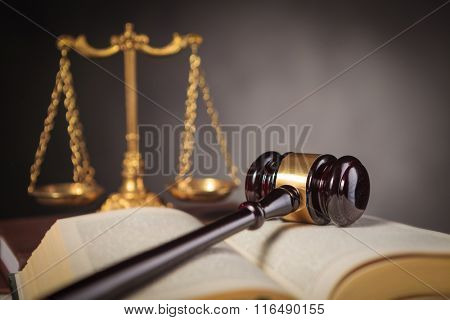 wooden judge's hammer on a law book near scale, law and justice concept