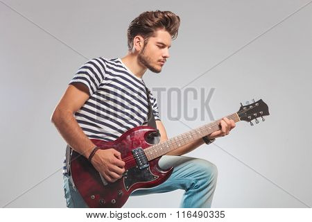 side photo of artist in studio background playing guitar with leg up while looking down