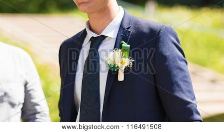 the groom in a blue suit with a buttonhole of flowers and greenery
