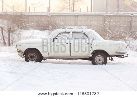 Abandoned Car Covered With Snow In Winter At Sunset, Warm Tones, Side View. Rusting, Recycling, Meta
