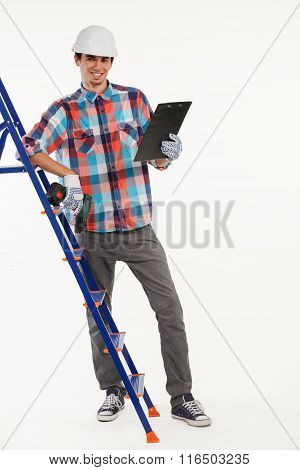 Constructor with hand drill on ladder.