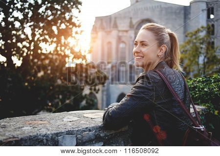 Young smiling woman traveler enjoying town landscape while standing outdoors against big old church