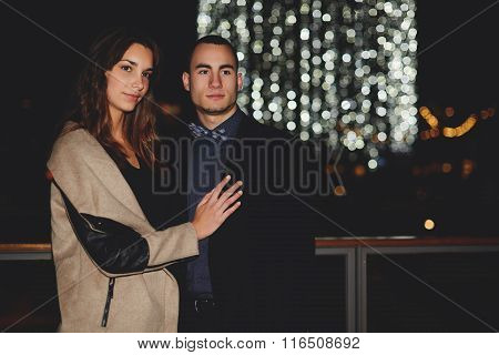 Young couple in love dressed in autumn clothes looking away while standing outside in evening