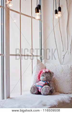 Beautiful Teddy Bear Sitting On A White Bed By The Window