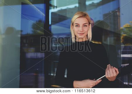 Confident woman entrepreneur holding digital tablet and look at the camera with smile