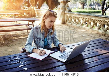 Young female student writes information from portable net-book while prepare for lectures