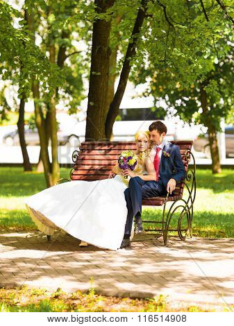 Bride and groom  on the bench in a park