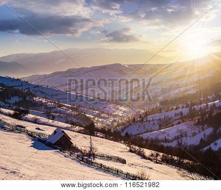 Woodshed On The Hillside In Winter Mountains At Sunset