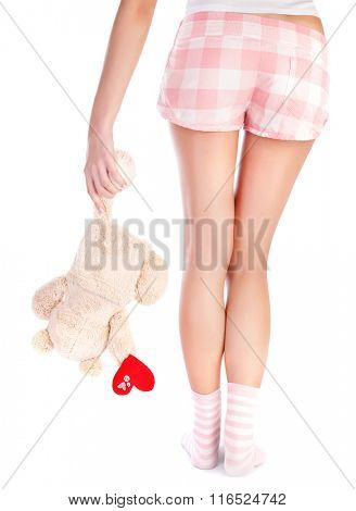 Back side of woman wearing pajamas holding soft toy of bear with red heart in hand, body part, isolated on white background, one-sided love concept