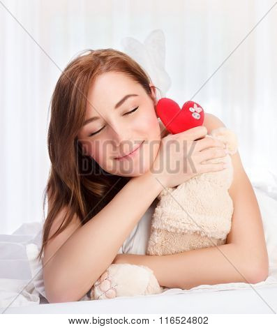Closeup portrait of cute young girl lying down in her bed at home, closing eyes of pleasure, receive soft bear toy with red heart as gift for Valentine day