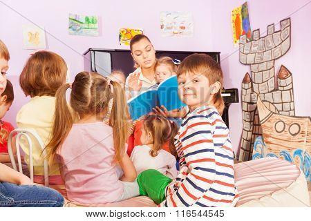 Kids sit around teacher and listening to story