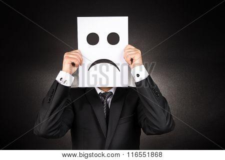Businessman holding paper with sad emoji