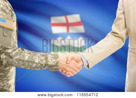 Usa Military Man In Uniform And Civil Man In Suit Shaking Hands With Canadian Province Flag On Backg