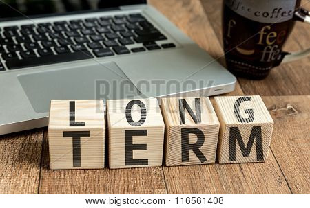 Long Term written on a wooden cube in a office desk