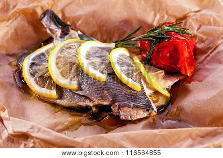 baked fish close-up decorated with lemon and rosemary
