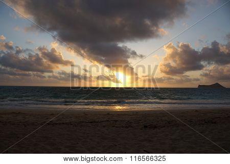 Early Morning Sunrise On Waimanalo Beach Over Ocean Bursting Through The Clouds