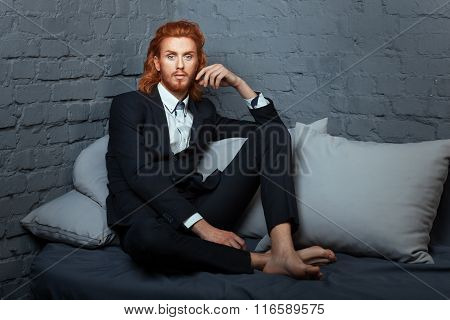 On the bed a man with freckles and red hair. He wore a stylish suit. poster