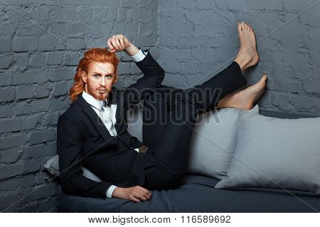 On The Sofa With His Feet Is Fashionable Guy.
