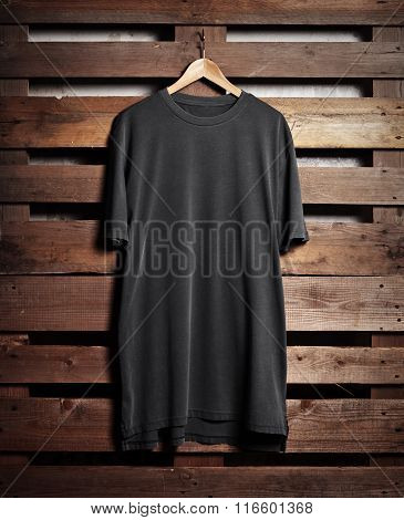 Picture of black tshirt hanging on wood background