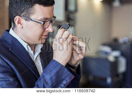 Jeweler Examining Diamond Through Loupe