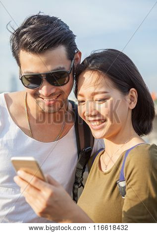 Younger Asian Man And Woman Looking To Smart Phone