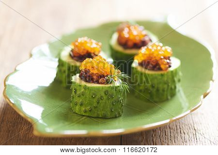 Cucumber appetizers with red caviar and black rice