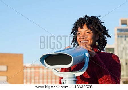 Young woman looking across holding a binoculars. Happy african woman standing with a binocular on a bright sunny day. Young african woman enjoyinng her vacation.