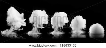 Different white smoke explosions isolated on black background