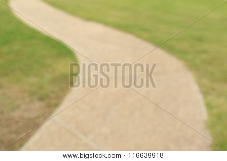 Blurred Photo Of Pathway Curving Through Green Lawn In Golf Course.