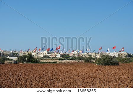 A lot of flags in the small maltese village on summer fest day, Malta Zurieq village, small village in Malta, Zurieq view, flags record day in small maltese village. Maltese feast. Festival poster