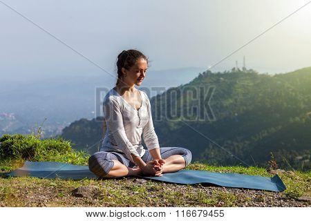 Sporty fit woman practices yoga asana Baddha Konasana - bound angle pose outdoors in HImalayas mountains in the morning. Himachal Pradesh, India poster