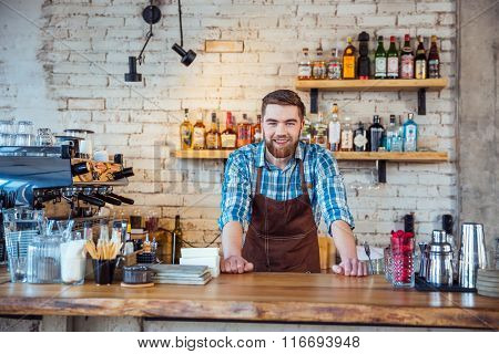 Happy attractive young bearded barista in brown apron at work in cafeteria