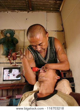 A disabled dentist with no hands files a patient's teeth at his dental clinic in Jakarta, Java