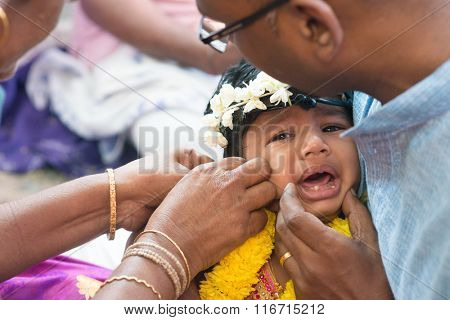 Baby girl crying in the karna vedha events. Traditional Indian Hindus ear piercing ceremony. India special rituals.