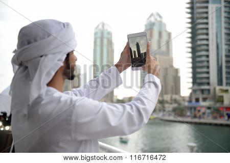 Young Emirati arab man taking photo
