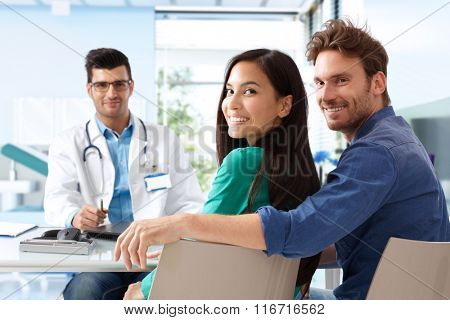 Happy young attractive couple sitting at doctor's room on consultation.