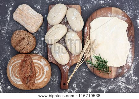 Fresh dough for bread making with ciabatta and seeded rolls and  rye loaf with wheat sheaths and rosemary herb and flour dusting over grey background.