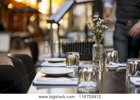Cafe table in laneway.  Focus on Flowers.
