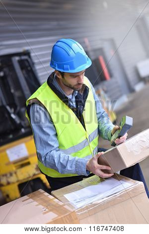 Warehouseman on dock scanning products ready for shipment