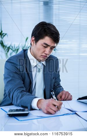 Troubled asian businessman in his desk writing somethings