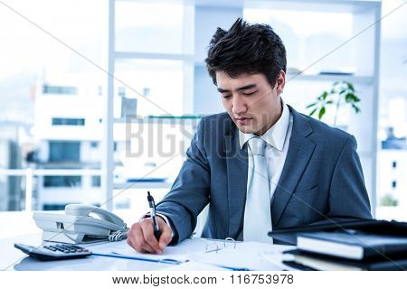 Concentrated asian businessman writing something is his office