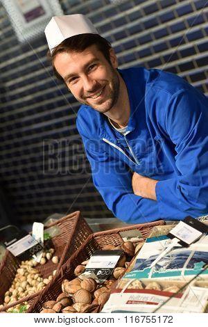 Portrait of smiling fishmonger with blue uniform